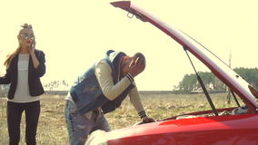 Young man repair a car and his angry girlfriend talking phone in the field. Couple repair a broken car in the field stock video footage