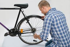 Young Man Repairing Bike Royalty Free Stock Image