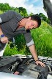 Young man repairing broken car Stock Images
