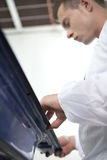 Young man repairing car door. Man wearing overall and working in shop Stock Photos