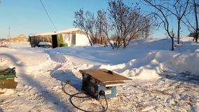 Young man repairing, circular saw, winter on the street, in the countryside stock video