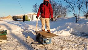 Young man repairing, circular saw, winter on the street, in the countryside stock footage