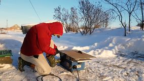 Young man repairing, circular saw, winter on the street, in the countryside stock video footage