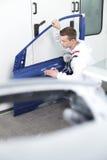 Young man repairing door in car. Stock Image