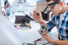Young man repairing drones chip with a screwdriver. Necessary but hard. Young handsome concentrated man repairing drones chip and using screwdriver while stock images
