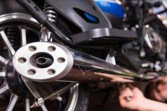 Young man repairing his motorbike Stock Images