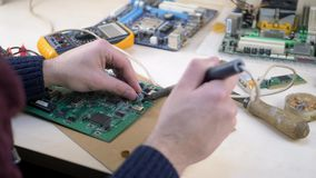 Young man repairing motherboard from PC. Repair shop and electronic devices concept stock footage