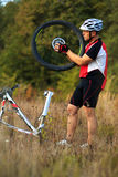 Young man repairing mountain bike in the forest Royalty Free Stock Photos