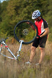 Young man repairing mountain bike in the forest Royalty Free Stock Images