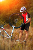 Young man repairing mountain bike in the forest Stock Photos