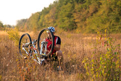 Young man repairing mountain bike in the forest Stock Image
