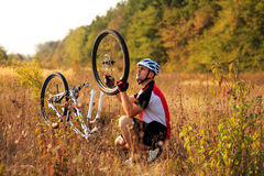 Young man repairing mountain bike in the forest Royalty Free Stock Photography