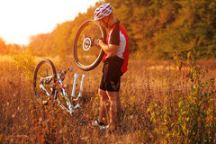 Young man repairing mountain bike in the forest Stock Photography