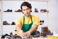The young man repairing shoes in workshop. Young man repairing shoes in workshop stock photos