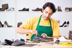 The young man repairing shoes in workshop. Young man repairing shoes in workshop stock images