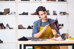 Young man repairing shoes in workshop. The young man repairing shoes in workshop royalty free stock images