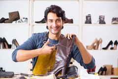 Young man repairing shoes in workshop. The young man repairing shoes in workshop royalty free stock photography