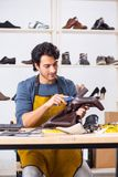 The young man repairing shoes in workshop. Young man repairing shoes in workshop royalty free stock photos