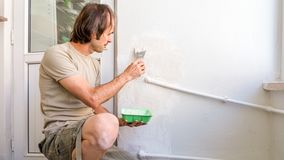 Young man repairing wall at his apartment, applying plaster mix on the wall royalty free stock photos