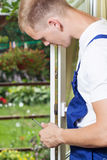 Young man repairing a window Royalty Free Stock Images