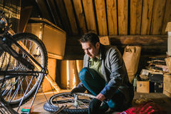 Young man repairs the bicycle in garage Royalty Free Stock Photography