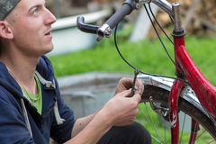 Young man repairs a bicycle Royalty Free Stock Images