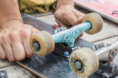 Young man repairs a skateboard and changes wheel sets. In a home workshop royalty free stock photography