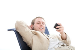 Young man rest in chair and listens digital player Stock Image
