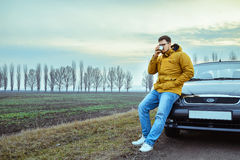Young man rest near the car, drinks hot tea Stock Image