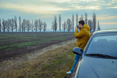 Young man rest near the car, drinks hot tea Royalty Free Stock Photo