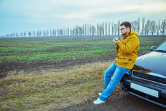 Young man rest near the car, drinks hot tea Royalty Free Stock Photography