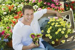 Young man resting on bench in garden centre Royalty Free Stock Images