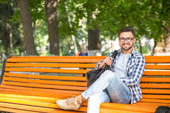 Young man resting on the bench outdoors. Young man resting on the bench after his hard working day. Smiling man sitting with a bag outdoors in the park and royalty free stock photo