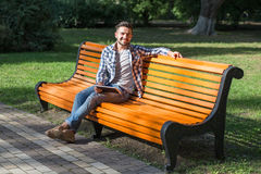 Young man resting on the bench outdoors. Young man looking at the camera and sitting on the bench in the park. Short-haired man smiling for photographer outdoors royalty free stock images