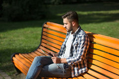 Young man resting on the bench outdoors Stock Photography