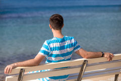 Young man resting on bench on the sea Royalty Free Stock Images