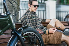Young Man Resting On Bench And Using Tablet Communication Connection Digital Devices Technology Concept. Handsome young guy in sunglasses resting on bench next Stock Images