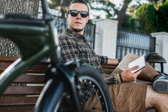 Young Man Resting On Bench And Using Tablet In Summer Park Communication Connection Digital Devices Technology Concept. Handsome young guy in sunglasses resting Stock Image