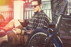 Young Man Resting On Bench And Using Tablet, Toned And Scratches. Handsome young guy in sunglasses resting on bench next to bicycle. Person uses a digital tablet royalty free stock photography