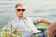 Young man resting in boat. Portrait of a young handsome man resting in a boat on the lake, looking at camera, sunny summer day Stock Images