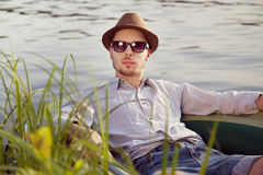 Young man resting in boat. Portrait of a young handsome man resting in a boat on the lake, sunny summer day Stock Image