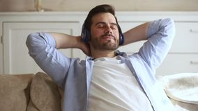 Young man resting on couch listens to music through headphones. Young serene man resting in living room leaned on sofa put hands behind head listens to music stock video