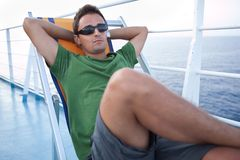 Young man resting on a deckchair. While traveling on a liner across a sea/ocean Stock Photos