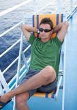 Young man resting on a deckchair. While traveling on a liner across a sea/ocean Royalty Free Stock Photos