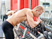 Young man resting on dumbbells rack after workout in gym. Handsome young athletic man resting on dumbbells rack after workout in gym Royalty Free Stock Photos