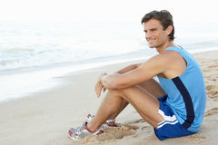 Young Man Resting After Exercise On Beach Stock Images