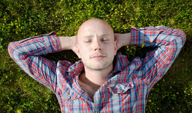 Young man resting in the grass. Handsome young man resting on the grass in the sun, with his hands behind his head Royalty Free Stock Photos