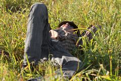 Young man resting in grass outdoors Royalty Free Stock Images