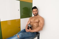 Man Resting In Locker Room With Shaker. Young Man Resting In Gym Dressing Room With Supplements Shaker for Copy Space - a Place for Your Text stock photo