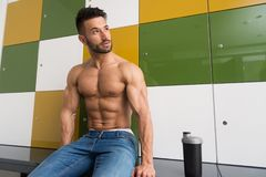 Man Resting In Locker Room With Shaker. Young Man Resting In Gym Dressing Room With Supplements Shaker for Copy Space - a Place for Your Text royalty free stock photography